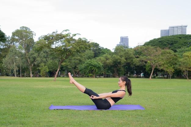 Frau übung yoga im park bereit für einen gesunden lebensstil in der natur