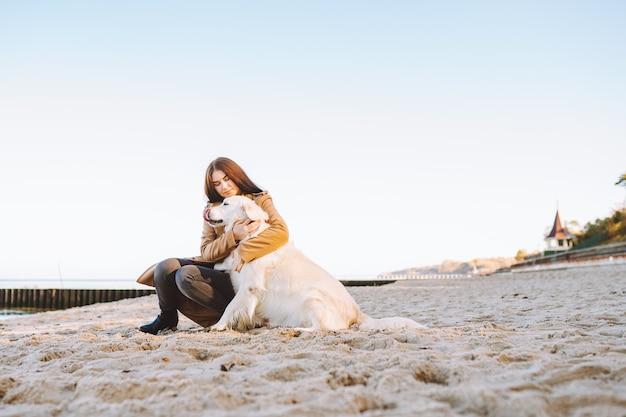 Frau umarmen mit ihrem goldenen retreiver hund am strand am warmen herbsttag