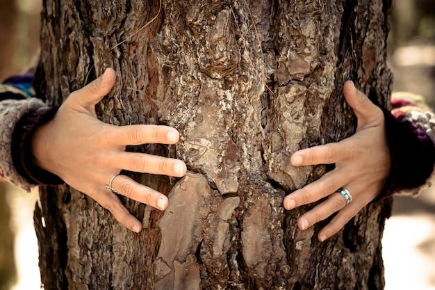 Frau umarmt baumrinde - finger mit ringen und liebesschutz-umwelt-naturkonzept für eine neue welt, die die naturräume im freien spürt - liebe und für immer mit bäumen zusammen