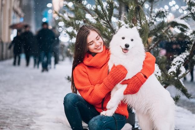 Frau umarmt ihren hund auf einer nachtstraße