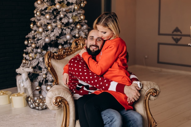 Frau umarmt ihren mann, der zart im weichen großen stuhl vor einem weihnachtsbaum sitzt