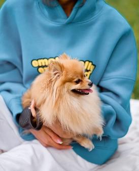Frau umarmt kleine hunde in einem park im freien