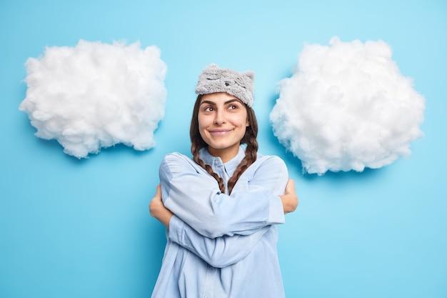 Frau umarmt sich selbst, verschränkt die arme, lächelt und sieht mit romantischem ausdruck aus, gekleidet in weiche schlafmaske, isoliert auf blau