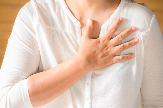 Frau umklammert ihre brust