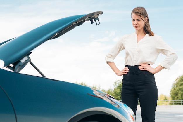 Frau und auto mit offener motorhaube