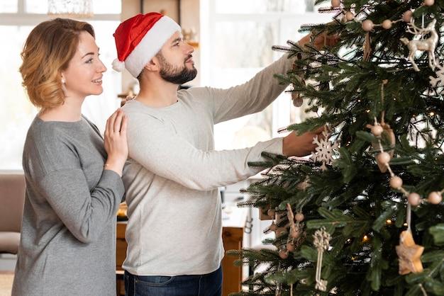 Frau und ehemann, die baum verzieren