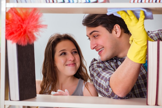 Frau und ehemann, die staub vom bücherregal säubern