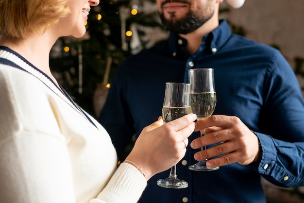 Frau und ehemann jubeln mit champagner am weihnachtstag