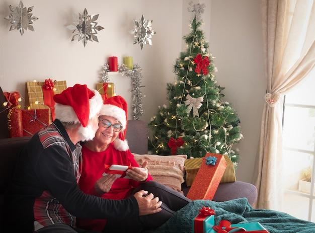 Frau und ehemann über 65 sitzen auf der couch mit weihnachtsmützen und feiern weihnachten. ein süßer kuss und viele geschenke für sie und die familie
