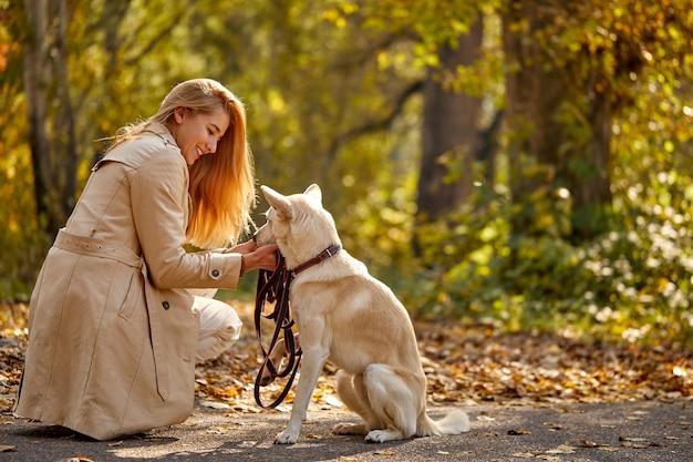 Frau und freundlicher netter hund im wald, blonde kaukasische frau im mantel unter abgefallenen blättern am sonnigen herbsttag