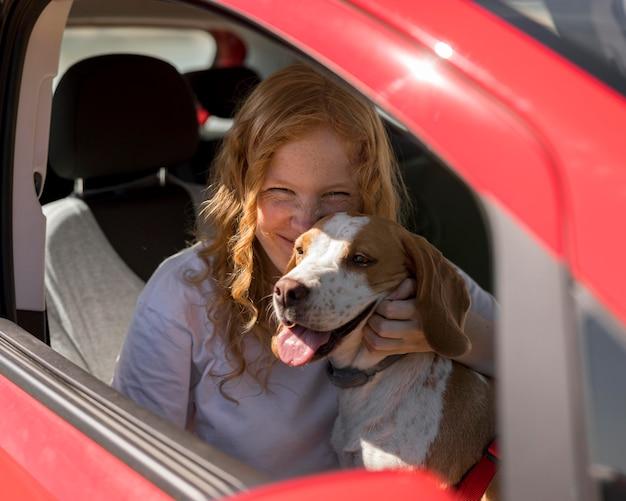 Frau und glücklicher hund gehen auf eine fahrt mit dem auto