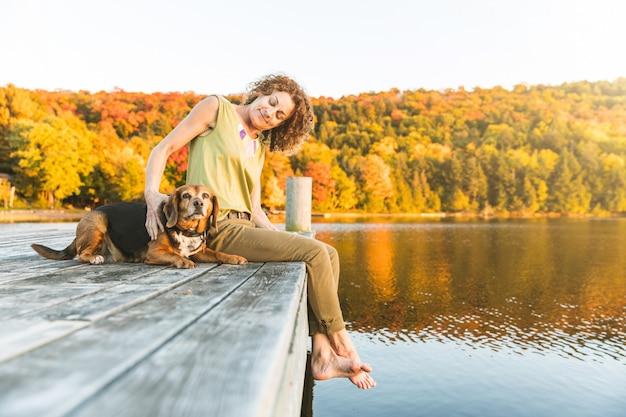 Frau und hund, die auf dem dock sich entspannen