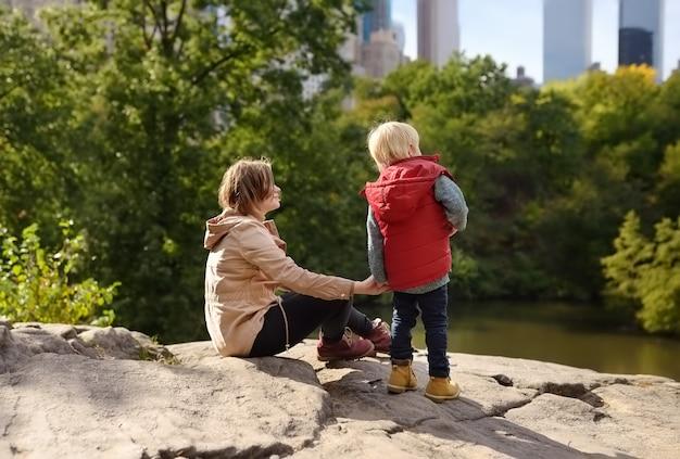 Frau und ihr charmanter kleiner sohn bewundern die aussicht im central park