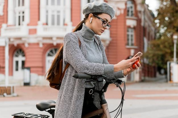 Frau und ihr fahrrad mit dem handy