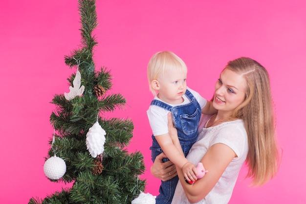 Frau und ihr kind posieren neben dem weihnachtsbaum