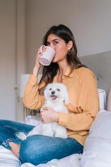 Frau und ihr netter hund zu hause, die tee trinken