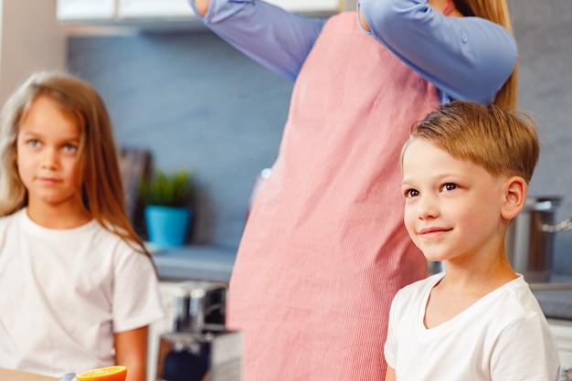 Frau und ihre kinder kochen in der küche