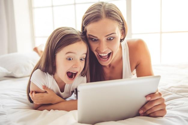 Frau und ihre kleine tochter benutzen eine digitale tablette