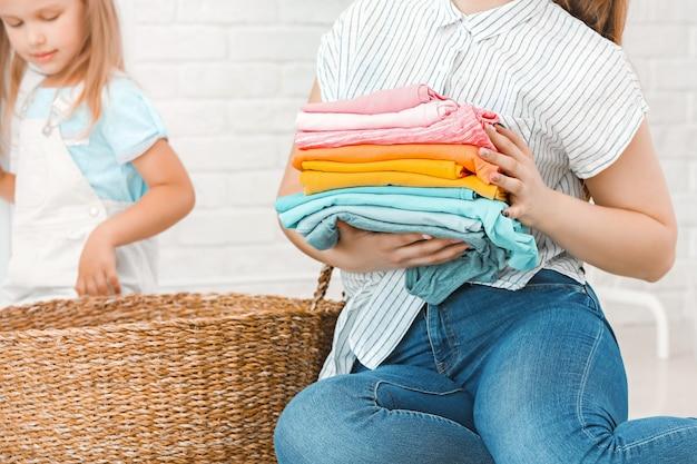 Frau und ihre kleine tochter, die zu hause wäsche waschen