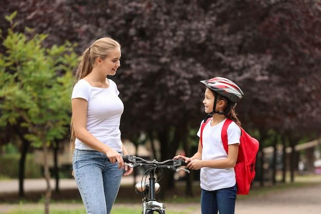 Frau und ihre kleine tochter mit fahrrad im freien