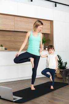 Frau und ihre kleine tochter stehen in einer baumpose, während sie zu hause zusammen yoga machen