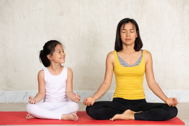 Frau und ihre reizend kleine tochter, die meditation tun