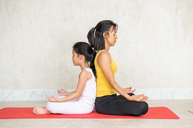 Frau und ihre reizend kleine tochter, die yoga tun