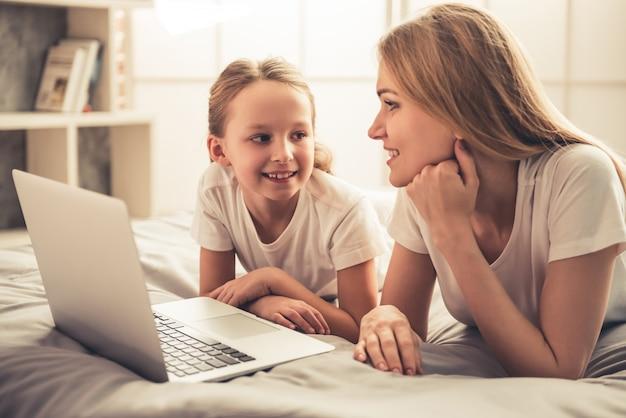 Frau und ihre süße kleine tochter benutzen einen laptop.