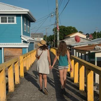 Frau und ihre tochter, die auf eine brücke, cayman cay, utila-insel, bucht-inseln, honduras gehen