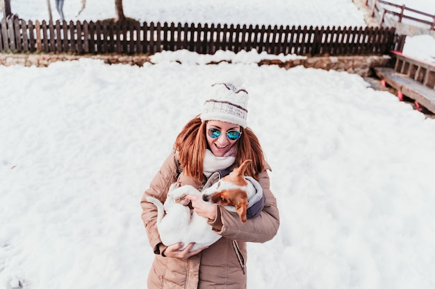 Frau und jack russell hund spielen im freien am berg. wintersaison