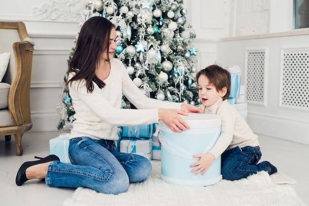 Frau und junge, die weihnachtsgeschenke überprüfen
