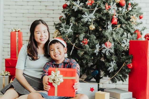 Frau und junge, die zusammen durch weihnachtsbaum mit geschenkboxen sitzen