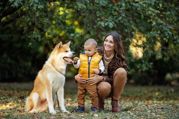 Frau und junge nahe dem roten hund am herbstpark