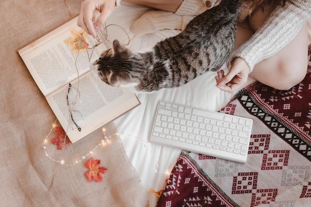 Frau und katze nahe buch und tastatur