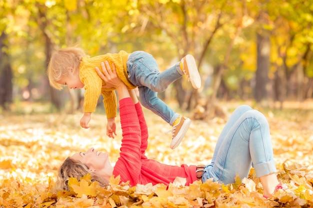 Frau und kind, die spaß im freien im herbstpark haben