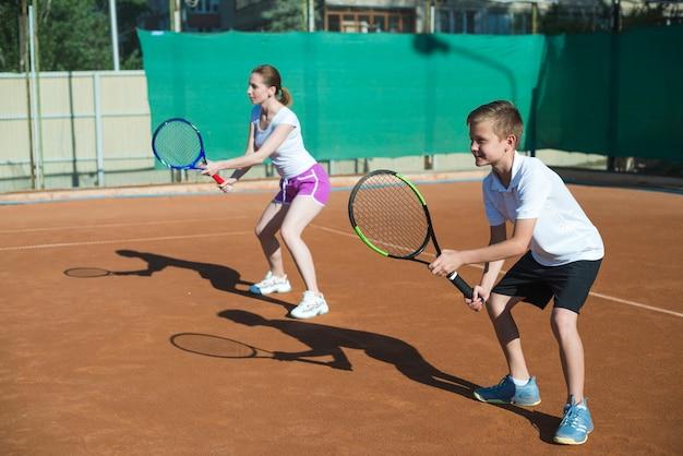 Frau und kind, die tennis spielen