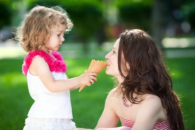 Frau und kind essen eis im frühlingspark