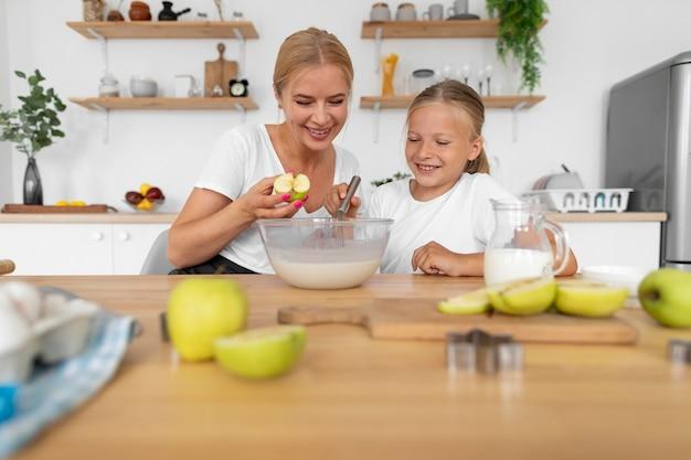 Frau und kind kochen mit mittlerer aufnahme
