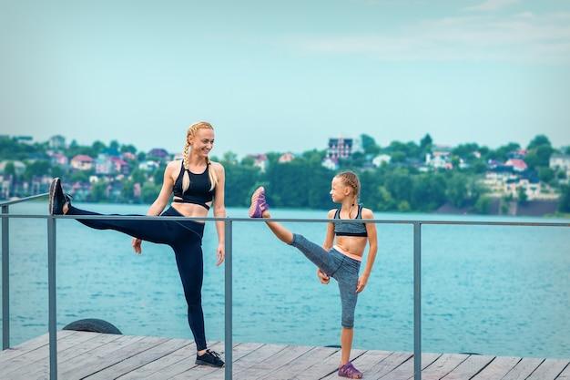 Frau und kind machen sportübungen und strecken ihre beine auf dem pier des sees