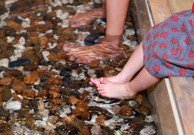 Frau und kind mädchen fuß einweichen onsen, fußbad an einer japanischen heißen quelle (onsen)