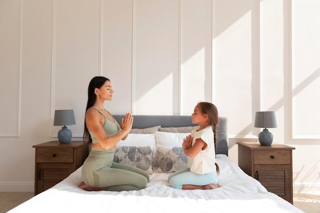 Frau und kind meditieren im bett voller schuss