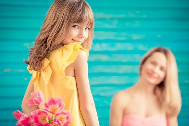Frau und kind mit blumenstrauß blumen vor grünem hintergrund familienurlaub konzept muttertag