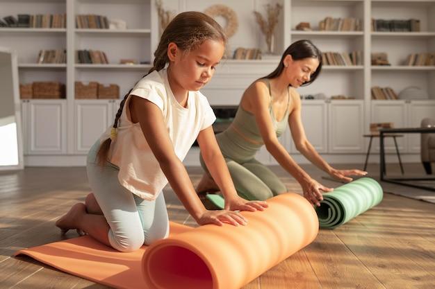 Frau und kind mit yogamatte voller schuss