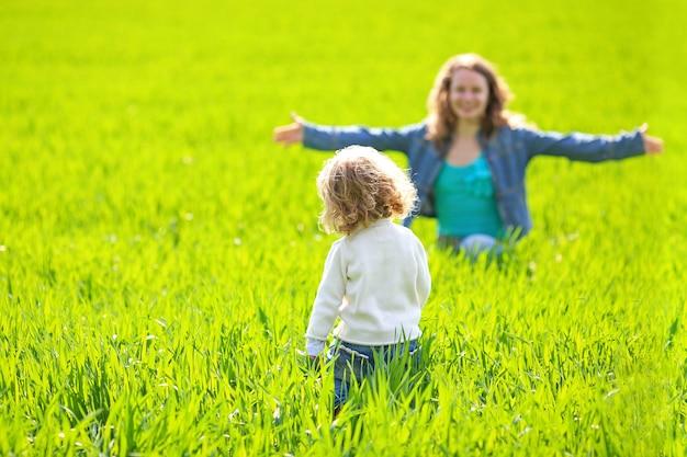 Frau und kind spielen verstecken im sommerfeld