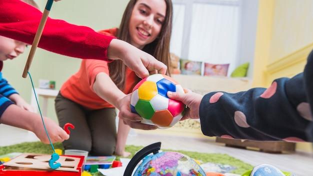 Frau und kinder spielen auf dem boden