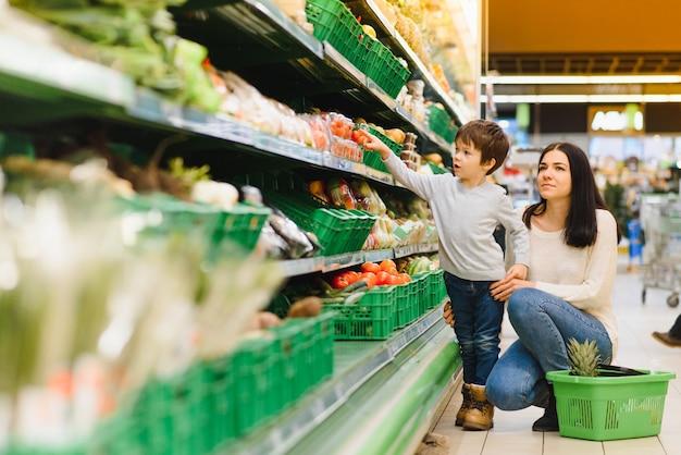 Frau und kinderjunge beim familieneinkauf mit trolley im supermarkt