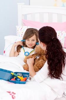 Frau und kleines mädchen, die mit einem stethoskop spielen