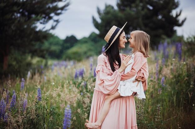 Frau und kleines mädchen in den rosa kleidern werfen auf dem feld von lavander auf