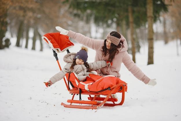 Frau und kleines mädchen in einem park mit einem schlitten