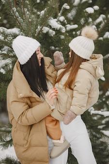 Frau und kleines mädchen in einem verschneiten park